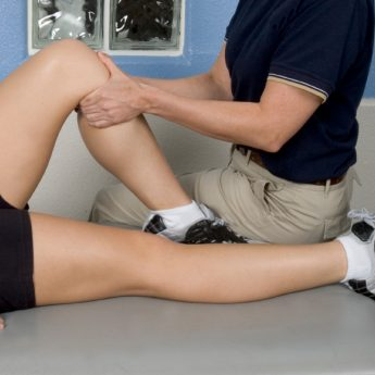 Massage Therapist working on a patient's knee